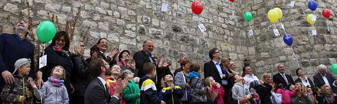 Kinder der Kindertagesstätte Spatzennest lassen zusammen mit den Teilnehmern der Vollversammlung Bündnis für Familie ihre Luftballons fliegen.