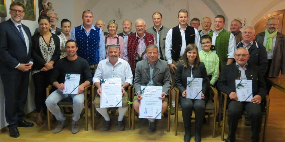 Landrat Martin Wolf (li.), Roland Gronbau (3.v.l.) und Heribert Reiter (re.) gratulierten den Gewinnern des diesjährigen Maibaumwettbewerbs und überreichten ihnen die entsprechenden Urkunden und Preise. (Foto: Appel)